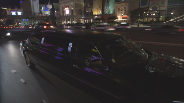 wide angle moving pov 3/4 left back of limo, car, or vehicle driving through las vegas strip. lights from clubs, nightclubs, hotels, resorts, and casinos. palm trees. - limousine stock videos & royalty-free footage