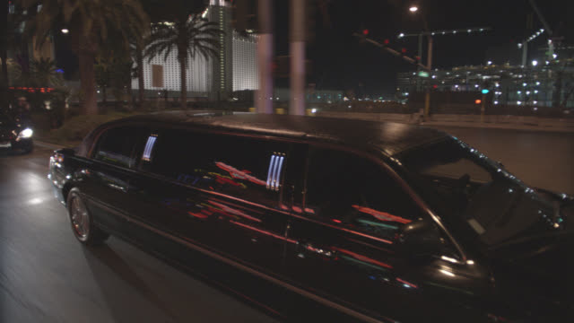 high angle down moving pov 3/4 left back above of limo, car, or vehicle driving through las vegas strip. lights from clubs, nightclubs, hotels, resorts, and casinos. palm trees. - limousine stock videos & royalty-free footage