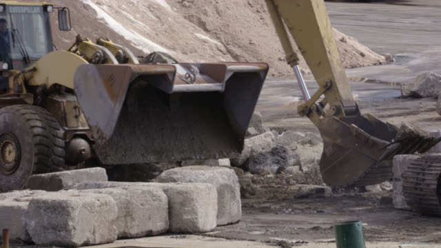 close angle of construction crane backing away from broken cement or stone. machinery. pile of sand in background. - crane construction machinery stock videos & royalty-free footage