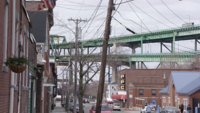 pan up of town or neighborhood street near harbor to maurice j. tobin memorial bridge (or mystic river bridge). red brick buildings surround streets. could be warehouses or shipyards. ppc and american flags visible in background. people cross the street. - american red cross stock videos & royalty-free footage