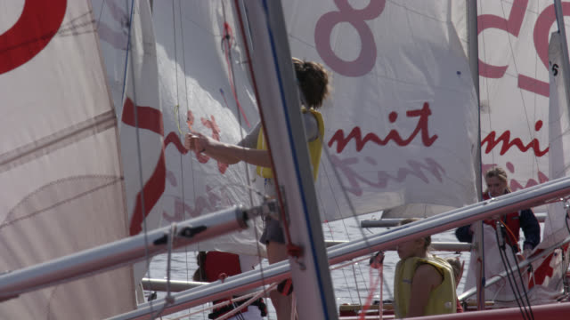 close angle of women, students, or young women on red sailboats at dock or pier working on rigs. charles river. mit sailing team and sailing pavilion. mit visible on sails. could be marina. university or college. - river charles stock videos & royalty-free footage