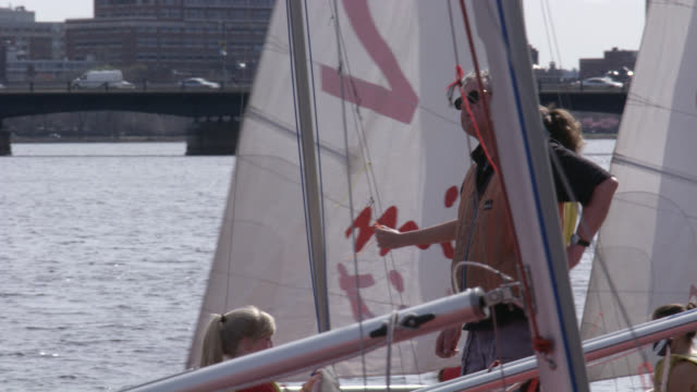 hand held of women or young women on red sailboats at dock, pier, or marina working on rigs. charles river. instructor comes over to help. mit sailing pavilion. mit visible on sails. could be sailing crew, team or class. university or college. - river charles stock videos & royalty-free footage