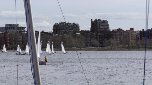 wide angle of charles river with sailboats. boat passes by. - river charles stock videos & royalty-free footage