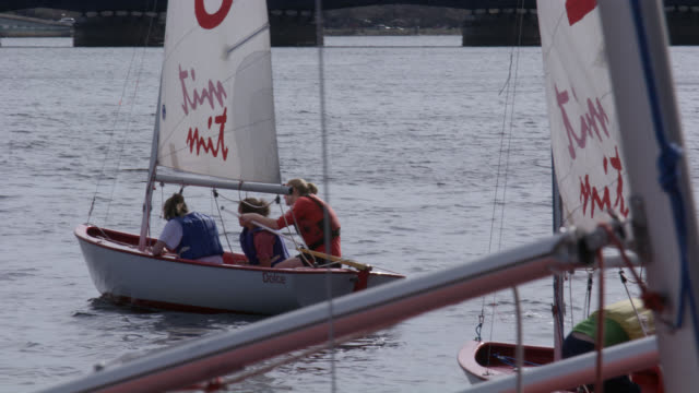 medium angle of sailboats on a dock or pier with charles river in background. sailboats sail off with mit on sails. could be sailing crew, team, or class. university or college. harvard bridge. - river charles stock videos & royalty-free footage