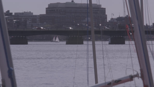 close angle of sailboat masts on pier or dock on charles river. mit sailing pavilion. sailing. harvard bridge visible, see citgo sign. could be marina. university or college. - river charles stock videos & royalty-free footage