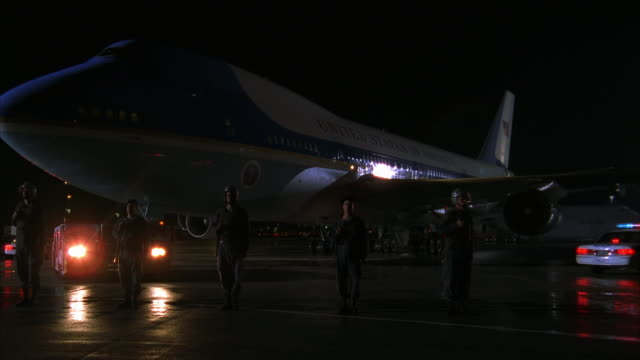 PAN LEFT TO RIGHT OF AIR FORCE ONE JET PARKED ON RUNWAY. SOLDIERS STAND AT ATTENTION AROUND PLANE NEXT TO POLICE CARS WITH LIGHTS ON. PLANE BEGINS TO TAXI TOWARD CAMERA, CAMERA PANS AROUND FRONT OF PLANE AND STOPS TO VIEW SIDE OF JET.