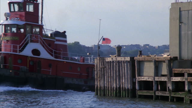 medium angle of hudson river facing new jersey in background. boat dock and building in foreground. red tugboat with american flag pulls barge with junk or garbage, appears from right and moves across to left. police car on top of garbage, see two tall to - barge stock videos & royalty-free footage