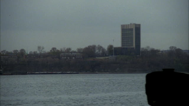 medium angle of hudson river and river bank. see office building and trees on bluff above river bank. red tugboat enters screen on right towing barge loaded with trash bags. see police car on barge covered in trash bags. pans left to follow police car in - barge stock videos & royalty-free footage