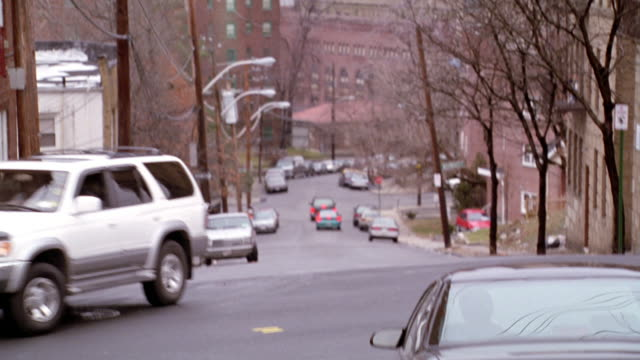 MEDIUM ANGLE OF TRAFFIC SIGNAL WITH RED SIGNAL LIT. SEE APARTMENT BUILDINGS ON RIGHT AND LEFT SIDES. SEE PHONE AND ELECTRICAL LINES ACROSS SCREEN. SEE SMOKE STACK IN BACKGROUND. SEE TREE COVERED HILL IN FAR BACKGROUND. LIGHT TURNS GREEN AND CAMERA PANS DO
