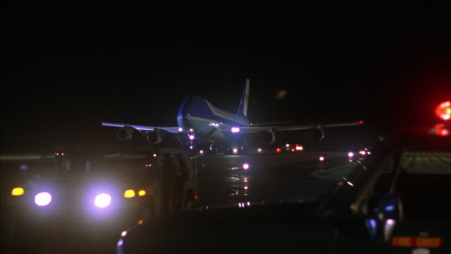 MEDIUM ANGLE OF LIT RUNWAY AT NIGHT. SIREN OF FIRE SUV FLASHES IN FOREGROUND, MAN IN DRIVER'S SIDE. SEE AIR FORCE ONE AIRPLANE APPEAR FROM DISTANCE, AIRPLANE DESCENDS AND LANDS. SEE JEEPS GUIDING IN FRONT OF AIRPLANE ON RUNWAY. HEADLIGHTS OF THREE CARS WI