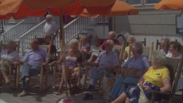 stockvideo's en b-roll-footage met medium angle of elderly people sitting in rocking chairs on outdoor deck or patio under large orange sun umbrellas. probably at beach during summer. see one woman with bathing suit on. - schommelstoel