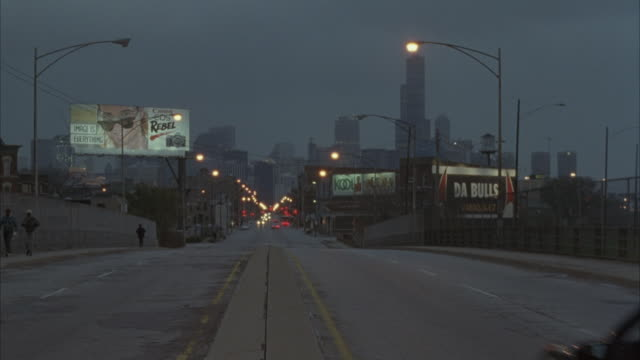 vidéos et rushes de medium angle of city street, pov in center divider of street. see chicago skyline in background with sears tower. see police motorcade drive by and past pov on right. motorcade consists of police cars, police motorcycles and a white news van in rear. - tour sears