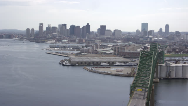 aerial over residential and commercial areas in inner city boston. flying across charles river. see leonard zakim bunker hill memorial bridge and downtown financial district. skyscrapers, high rises, and urban areas. - river charles stock videos & royalty-free footage