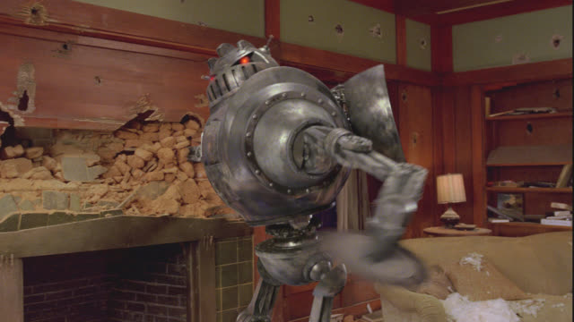 MEDIUM ANGLE OF ROBOT TEARING UP TILE AND BRICK FIREPLACE WALL IN DAMAGED HOUSE. OUTERSPACE SEEN OUTSIDE WINDOW.