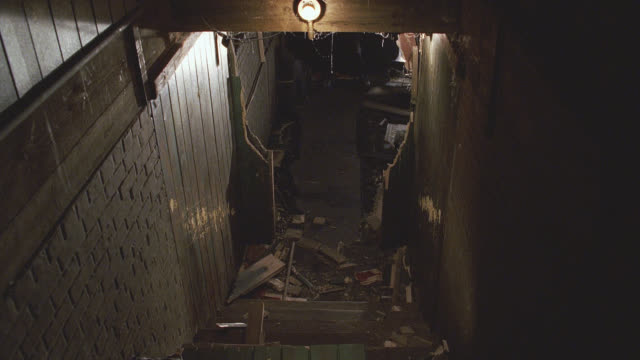 MEDIUM ANGLE OF ROBOT RUNNING TOWARDS CAMERA TO BASE OF STAIRCASE. ROBOT HAS GLOWING RED EYES AND ANTENNAS. SEE SPLINTERED DOORWAY AND DEBRIS ON GROUND. SEE EXPOSED LIGHT BULB ABOVE STAIRWELL. COULD BE STAIRS LEADING FROM A BASEMENT. MACHINES. DOORS.