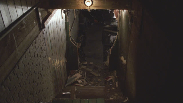medium angle of robot running towards camera to base of staircase. robot has glowing red eyes and antennas. see splintered doorway and debris on ground. see exposed light bulb above stairwell. could be stairs leading from a basement. machines. doors. - glowing doorway stock videos & royalty-free footage