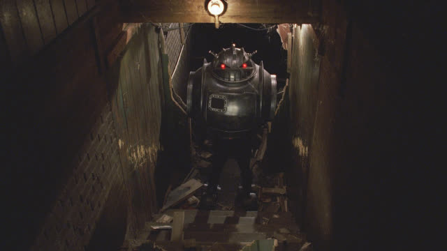 medium angle or robot running towards camera to base of staircase, stopping and backing away. series. metal robot has glowing red eyes and antennas. debris and damaged doorway visible. machines. doors. basements. - glowing doorway stock videos & royalty-free footage
