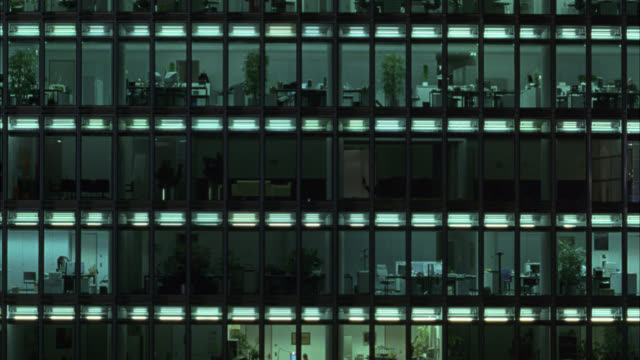 MEDIUM ANGLE OF SONY CENTER BERLIN, POTZDAMER PLATZ, HIGH RISE MODERN OFFICE BUILDING. GLASS WINDOWS. LIGHTS AND DESKS VISIBLE.