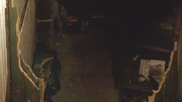 medium angle of robot running up path as seen through splintered doorway. robot has glowing red eyes and is made of metal. robot's eyes flash.  see antennas on head.  machines. - glowing doorway stock videos & royalty-free footage