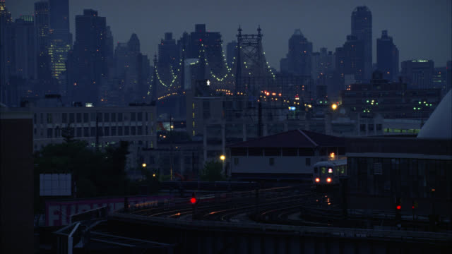 wide angle of subway train on elevated tracks in queens. queensboro bridge and manhattan city skyline in bg. urban area. skyscrapers, high rise and multi-story office or apartment buildings. fog. - building storey stock videos and b-roll footage