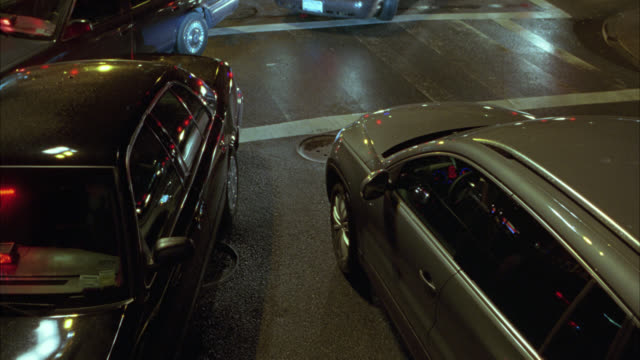high angle down of city street. near collision between  suv and nypd police cars with flashing lights and sirens. streets wet from rain. urban area. intersection. car stunts. - einsatzsirene stock-videos und b-roll-filmmaterial
