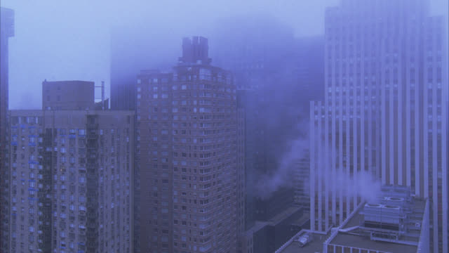 vidéos et rushes de wide angle of new york city skyline in fog. cars driving on city street below. high rises, office buildings, and apartment buildings. downtowns. - gratte ciel