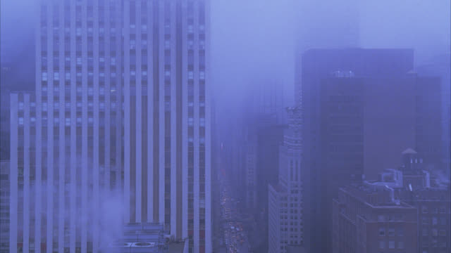 WIDE ANGLE OF NEW YORK CITY SKYLINE IN FOG. HIGH RISES, OFFICE BUILDINGS, AND APARTMENT BUILDINGS. DOWNTOWNS. CARS AND TRAFFIC ON CITY STREET BELOW.