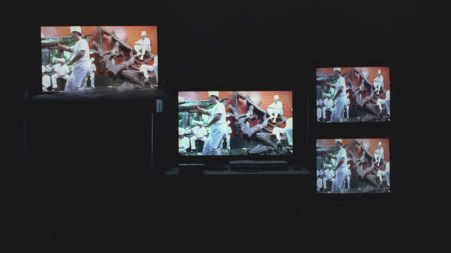 medium angle of video art exhibit. four digital video displays or  screens. could be art museum. fighting chefs and women making clothes in video. - digital signage stock videos & royalty-free footage