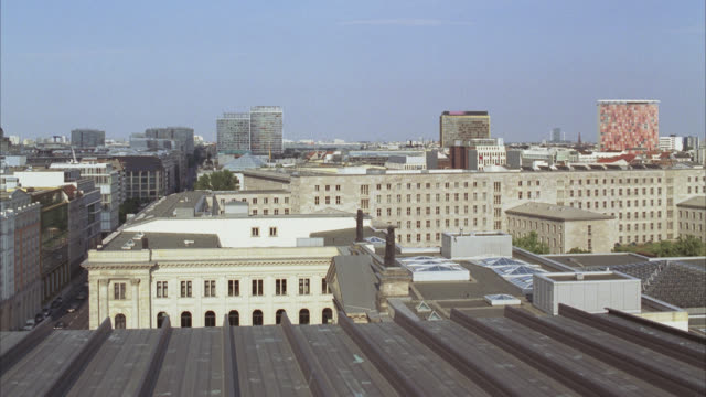 WIDE ANGLE OF ROOFTOPS AND ROOF OF APARTMENT BUILDINGS IN BERLIN. URBAN AREA. GLASS OFFICE BUILDINGS AND HIGH RISES VISIBLE IN BG.