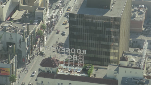 AERIAL OF HOLLYWOOD BOULEVARD. ROOFTOPS OF CALIFORNIA LANDMARK KODAK THEATRE, GRAUMAN'S CHINESE THEATRE, ROOSEVELT HOTEL, EL CAPITAN THEATRE AND MULTI-STORY OFFICE BUILDINGS. PEOPLE RUNNING PAST FILM CREW AND EQUIPMENT ON CITY STREET.