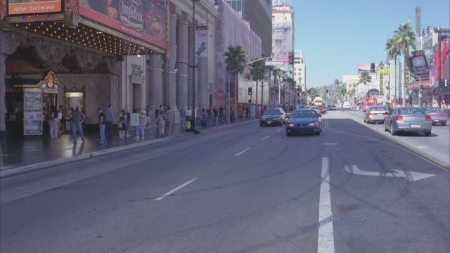 wide angle of cars and suvs driving down sunset strip. pedestrians and tourists on sidewalks watch as cars suddenly swerve. broken windows and shattered glass as if something fell into street. car stunts, crashes, and special effects. - traffic accident stock videos & royalty-free footage