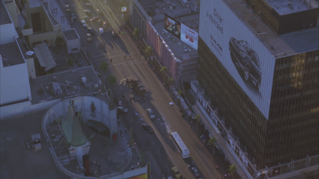aerial of  hollywood blvd and rooftops of hollywood landmarks: kodak theatre, grauman's chinese theatre, and roosevelt hotel. crashed or overturned semi truck or emergency or disaster stops traffic in city street outside of multi-story, high rise, office - mann theaters stock videos & royalty-free footage