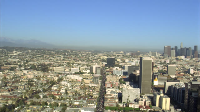 aerial of buildings and cityscape of los angeles. multi-story office buildings or skyscrapers of downtown including landmarks: us bank tower, aon center, 777 tower,  bank of america tower and wells fargo tower. smog over mountains behind los angeles skyli - usバンクタワー点の映像素材/bロール