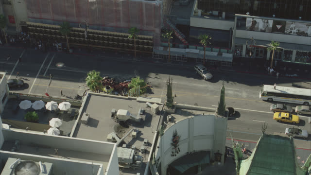 aerial of hollywood boulevard. rooftops of california landmark kodak theatre, grauman's chinese theatre, roosevelt hotel, el capitan theatre and multi-story office buildings. people running past overturned fire truck or semi truck crashed in center of cit - el capitan theatre stock videos & royalty-free footage
