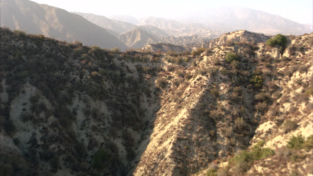 vídeos de stock, filmes e b-roll de aerial of rugged terrain of santa monica mountains dotted with shrubs. mountaintops or peaks. horizons. california. could be san gabriel mountains. - terreno extremo