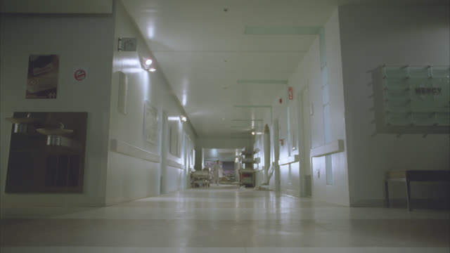 "WIDE ANGLE OF DOCTORS, NURSES OR EMERGENCY ROOM ATTENDANTS OR PEOPLE RUNNING FROM ROOM AT END OF LONG HOSPITAL HALLWAY. SIGN ON WALL INDICATES ""MERCY HOSPITAL."" WATER OR DRINKING FOUNTAIN, FLOOD LIGHTS AND GURNEYS ALONG WALLS."