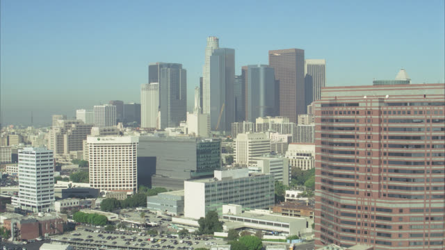stockvideo's en b-roll-footage met aerial of multi-story office buildings of downtown los angeles skyline or cityscape. landmark skyscrapers include: us bank tower, aon center and  bank of america tower. close on at&t switching center and mellon bank center. - us bank tower