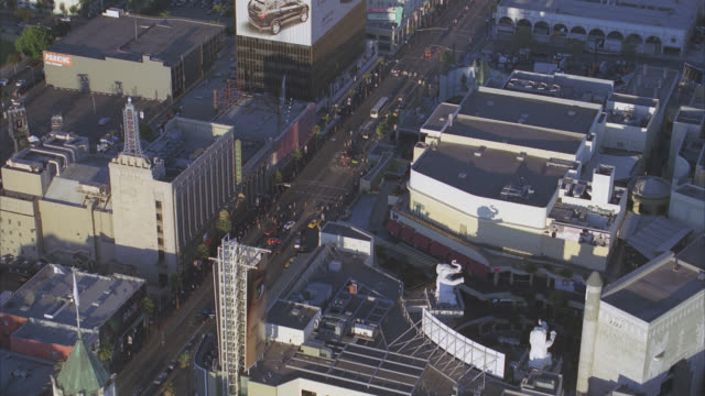 AERIAL OF CITY STREET INTERSECTION OF HOLLYWOOD BLVD AND VINE. ROOFTOPS OF HOLLYWOOD LANDMARKS: KODAK THEATRE, EL CAPITAN THEATRE, GRAUMAN'S CHINESE THEATRE, AND ROOSEVELT HOTEL. CRASHED OR OVERTURNED SEMI TRUCK OR EMERGENCY OR DISASTER STOPS TRAFFIC IN S