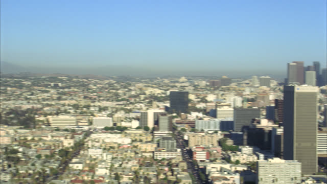 stockvideo's en b-roll-footage met aerial of buildings and cityscape of los angeles. multi-story office buildings or skyscrapers of downtown including landmarks: us bank tower, aon center, 777 tower,  bank of america tower and wells fargo tower. smog over mountains behind los angeles skyli - us bank tower