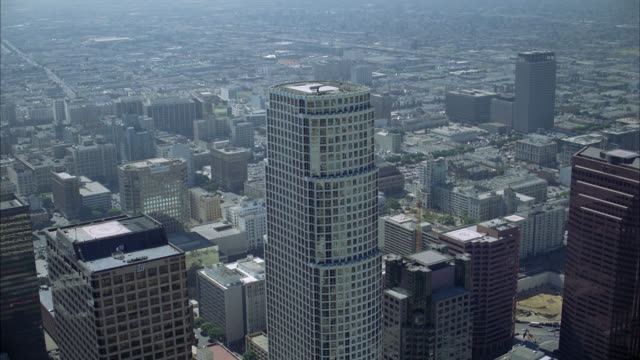 vídeos de stock, filmes e b-roll de aerial of 777 tower and other skyscrapers or multi-story office buildings of downtown los angeles skyline. postmodern-style glass building. tilt to birdseye pov of landscaped plaza with modern- style pavilion or gazebo made of metal. helicopter landing pa - gazebo