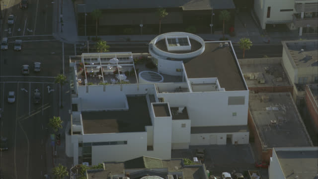 aerial of the paley center for media in beverly hills. white modern style building with glass rotunda situated on street corner. palm trees along sidewalk. late afternoon. rooftops of nearby businesses and buildings. museums. - paley center for media los angeles stock videos & royalty-free footage