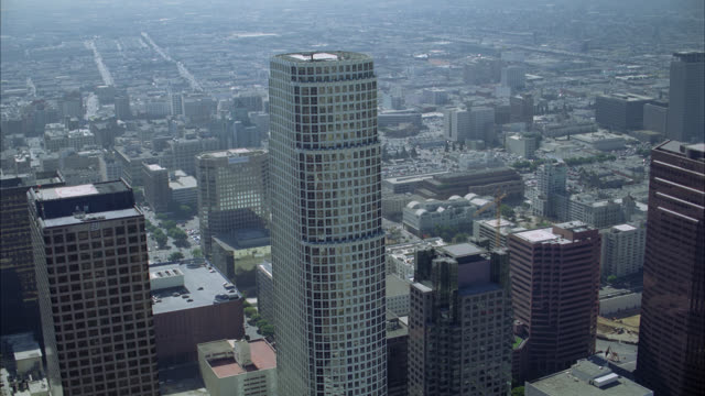 vídeos de stock, filmes e b-roll de aerial of 777 tower and other skyscrapers or multi-story office buildings of downtown los angeles skyline. postmodern-style glass building.  tilt to birdseye pov of landscaped plaza with modern- style pavilion or gazebo made of metal. helicopter landing p - gazebo