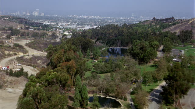 AERIAL OF PARK OR GOLF COURSE IN MIDST OF RUGGED TERRAIN OF HOLLYWOOD HILLS OR MOUNTAINS OUTSIDE OF LOS ANGELES. MOVES TO OFFICE BUILDINGS AND CITY STREETS. CITYSCAPES.  SKY OVERCAST WITH SMOG.