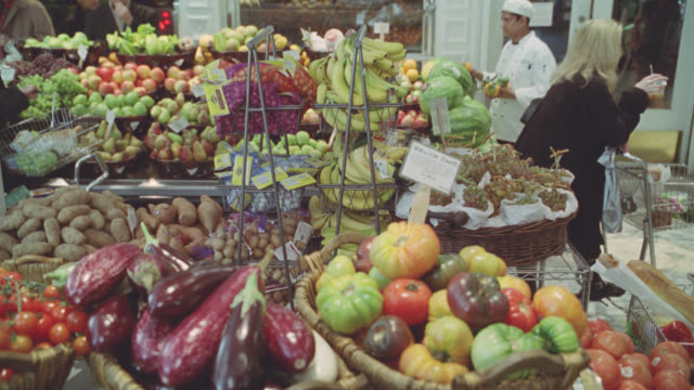 medium angle of grocery store or market produce. fresh fruits. bananas, apples, grape, and pears in bg. man in butcher uniform in bg. customers. shopping carts. pumpkins and eggplants in fg. - obst stock-videos und b-roll-filmmaterial
