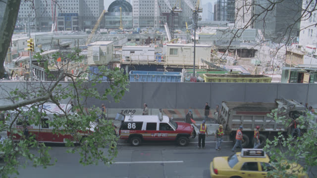 stockvideo's en b-roll-footage met high angle down of world trade center and chambers street subway entrance. iron fence with memorial flags and flowers. world trade center site in bg. construction site with garbage trucks, ambulances, and police officers. soldiers in camouflage stand near - memorial