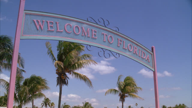 "UP ANGLE MOVING POV UNDER ""WELCOME TO FLORIDA"" SIGN. PALM TREES AND SKY."