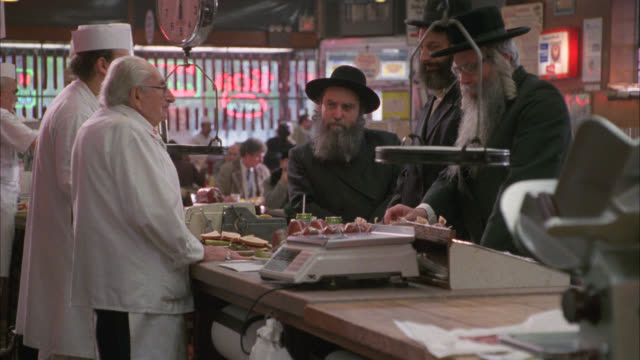 medium angle of counter in deli or restaurant. man behind counter hands customer a sandwich. katz or katz's delicatessen. lower east side. - 1980 stock videos & royalty-free footage
