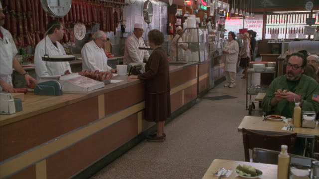 medium angle of counter in deli or restaurant. customers eating at tables. woman ordering at counter. katz or katz's delicatessen. lower east side. - 1980 stock videos and b-roll footage