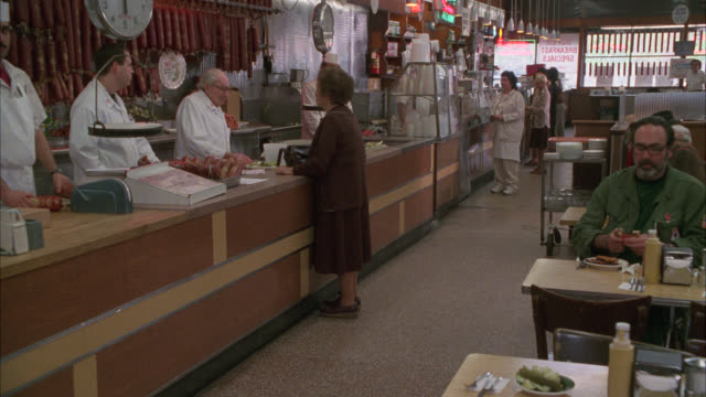 medium angle of counter in deli or restaurant. customers eating at tables. woman ordering at counter. katz delicatessen. - 1980 stock videos and b-roll footage