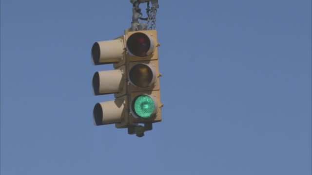 UP ANGLE OF TRAFFIC LIGHT OR SIGNAL CHANGING FROM GREEN TO YELLOW TO RED.